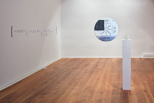 Identification Please, Liz Magic Laser, 2016, newspaper and video installation, installation view with The Invisible Cube, 2013, etched crystal, 4 x 4 x 4 in., edition of 5 and Inflective Medallion, 2015, enamel silkscreened on mirror, 47 x 47 x 0.25 in., Kunstverein Göttingen, Germany.