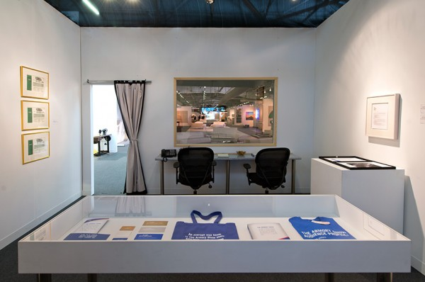 Artist's Proof, Liz Magic Laser, 2013, The Armory Show Centennial Edition art fair booth: modular hollow core panels, industrialcarpet, Luan plywood, MDF, laminate, aluminum metal, paint, office chairs, display monitors,display vitrine, acrylic glass, doorway, black curtain, curtain rod, two-way mirrored window,spotlights, The Armory Show Focus Group (2013) video, Sony 40 inchHD monitor, security camera and DVR system, and performance, 120 x 166 x 192 inches, installation view.